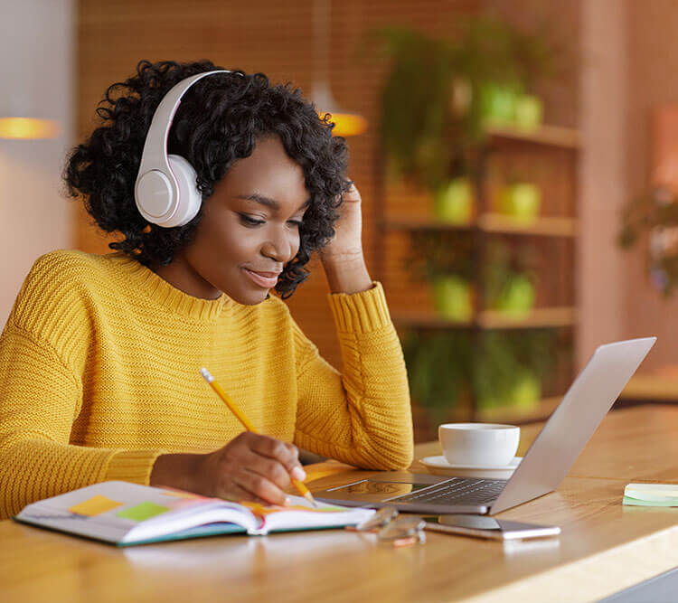 girl listening to head phones and doing computer work
